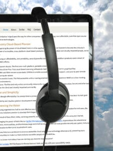 Headphones on a computer monitor showing text. Clouds in background.